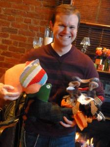 Dan holds a stack of the cutest, homespun stuffed friends courtesy of Kir's fellow crafters