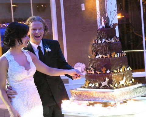 "Nicole & Christian cut their ""Winter Woodland"" cookie topped wedding cake"